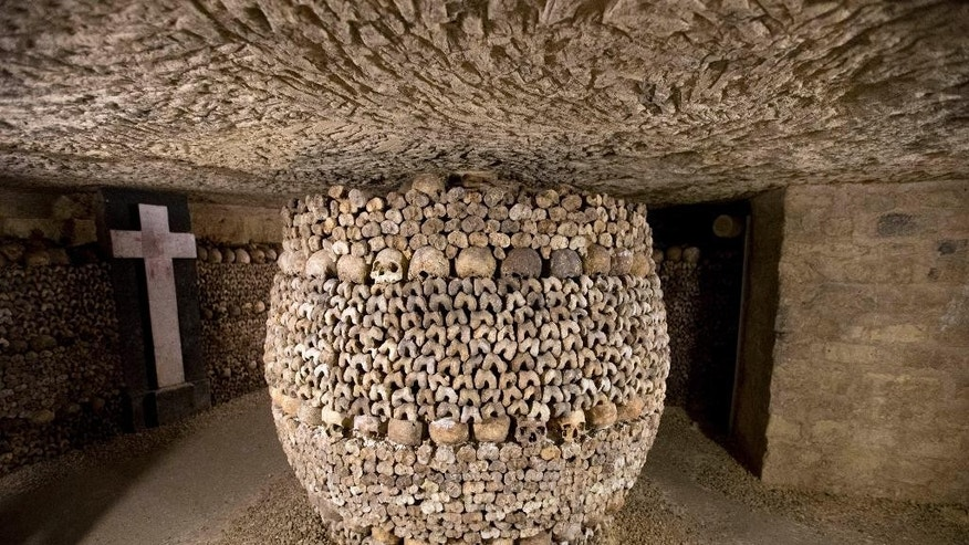 In this photo taken Tuesday, Oct. 14, 2014, skulls and bones are stacked at the Catacombs in Paris, France. The subterranean tunnels, stretching 2 kilometers (1.24 miles), cradle the bones of some 6 million Parisians from centuries past and once gave refuge to smugglers. The site used to close at 5 p.m., but is now staying open until 8 p.m. The change is mainly aimed at allowing more people to visit and reducing long lines, since it can only hold a limited number of people at a time and visits can't be reserved in advance. (AP Photo/Francois Mori)