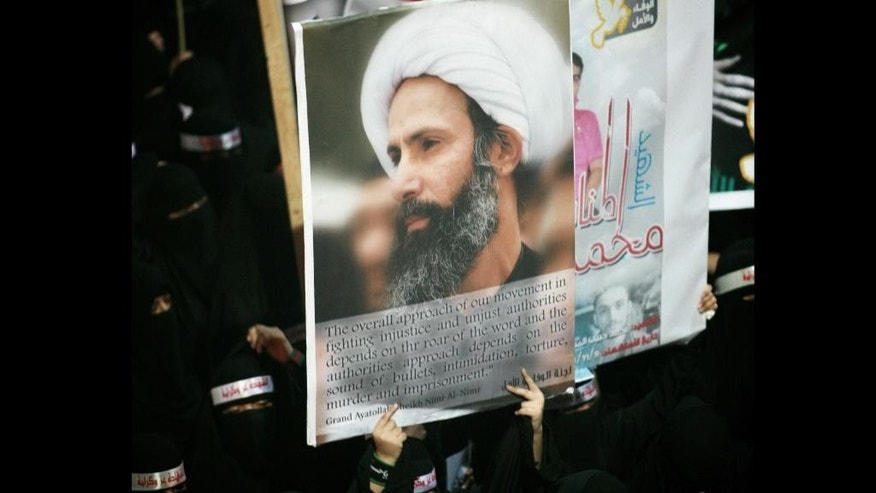 """FILE - In this Sunday, Sept. 30, 2012 file photo, a Saudi anti-government protester carries a poster with the image of jailed Shiite cleric Sheik Nimr al-Nimr during the funeral of three Shiite Muslims allegedly killed by Saudi security forces in the eastern town of al-Awamiya, Saudi Arabia. Mohammed al-Nimr, the brother of Nimr al-Nimr said Wednesday, Oct. 15, 2014, on Twitter that his brother has been sentenced to death by a court in Saudi Arabia. Shiite activist Jaafar al-Shayeb in eastern Saudi Arabia says the verdict appears to have been handed down for criminal offenses over the """"incitement"""" of Shiite protests in Saudi Arabia and neighboring Bahrain. The headbands read, """"martyrdom is honor and dignity."""" (AP Photo, File)"""