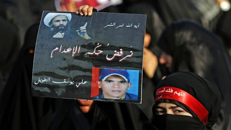 """FILE - In this Monday, April 1, 2013 file photo, a Bahraini woman holds up a sign opposing death sentences in Saudi Arabia against a Shiite cleric and in Bahrain against a young man facing charges for killing a policeman in 2011, during a funeral in Diraz, Bahrain. Arabic on the sign reads, """"Ayatollah Nimr al-Nimr, Ali Yousef al-Taweel, we reject the death sentences."""" Mohammed al-Nimr, the brother of Nimr al-Nimr said Wednesday, Oct. 15, 2014, on Twitter that his brother has been sentenced to death by a court in Saudi Arabia. Shiite activist Jaafar al-Shayeb in eastern Saudi Arabia says the verdict appears to have been handed down for criminal offenses over the """"incitement"""" of Shiite protests in Saudi Arabia and neighboring Bahrain. Arabic on her headband reads, """"God free our prisoners."""" (AP Photo/Hasan Jamali, File)"""