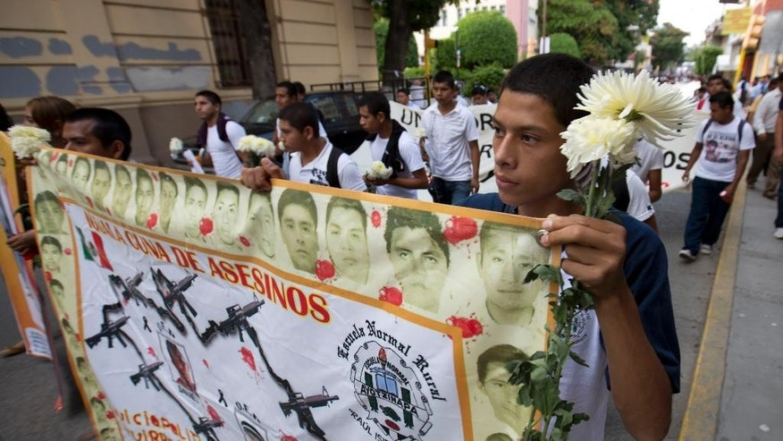 "Students hold a banner withe faces of the missing that reads in Spanish ""Iguala, cradle of murders,""  during a march with flowers and candles to protest the disappearance of 43 students from the Isidro Burgos rural teachers college in Chilpancingo, Mexico, Tuesday, Oct. 14, 2014. According to Mexico's attorney general none of the missing students were among the bodies found in the first set of mass graves outside the town. Authorities have said police involved in ""disappearing"" the students were working in conjunction with a local drug gang. (AP Photo/Eduardo Verdugo)"