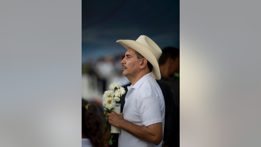 "A relative of missing students marches with flowers and candles to protest the disappearance of 43 students from the Isidro Burgos rural teachers college in Chilpancingo, Mexico, Tuesday, Oct. 14, 2014. According to Mexico's attorney general none of the missing students were among the bodies found in the first set of mass graves outside the town. Authorities have said police involved in ""disappearing"" the students were working in conjunction with a local drug gang. (AP Photo/Eduardo Verdugo)"