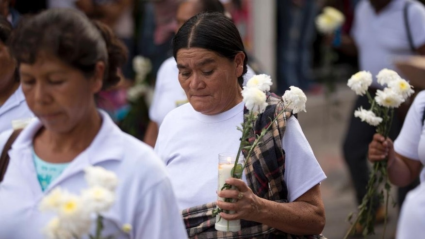 "Relatives of missing students march with flowers and candles to protest the disappearance of 43 students from the Isidro Burgos rural teachers college in Chilpancingo, Mexico, Tuesday, Oct. 14, 2014. According to Mexico's attorney general none of the missing students were among the bodies found in the first set of mass graves outside the town. Authorities have said police involved in ""disappearing"" the students were working in conjunction with a local drug gang. (AP Photo/Eduardo Verdugo)"