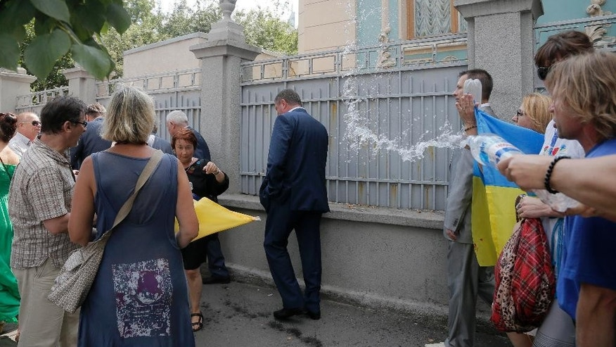 FILE - In this Tuesday, Aug. 12, 2014 file photo, activists throw water at various lawmakers as they demonstrate to demand sanctions against Russia, during a protest opposite the parliament building in Kiev, Ukraine. In Ukraine, trashing a politician isn't a metaphor. It's literal: Find a suspected shady official, grab him and throw him into a dumpster. The fad is part of a broader coarsening of the political climate in Ukraine as anger simmers over the snail's pace of reforms and persisting corruption since the overthrow in February of former President Viktor Yanukovych. (AP Photo/Efrem Lukatsky, File)