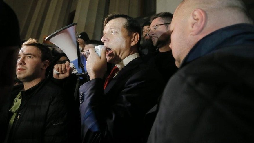 FILE - In this Thursday, March 27, 2014 file photo, Ukrainian lawmaker Oleh Lyashko, center, talks to members of the ultra nationalist right wing Right Sector group as they block the parliament building in Kiev, Ukraine. With parliamentary elections planned at the end of the month, the mood in Ukraine seems best suited to favor the chances of militantly nationalist rabble-rousers. A recent surge in support for abrasive rabble-rouser Oleh Lyashko, whose Radical Party is expected to be one of a handful of parties that will gain entry into parliament in the Oct. 26 election, marks a distinct turn against political order. (AP Photo/Efrem Lukatsky, File)