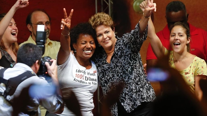 Brazil's President Dilma Rousseff, who is running for re-election with the Workers Party, second from right, poses for photos as campaigns at a rally in Sao Paulo, Brazil, Wednesday, Oct. 15, 2014. Rousseff will face rival candidate Aecio Neves, from the Brazilian Social Democracy Party, in a presidential runoff on Oct. 26. (AP Photo/Andre Penner)
