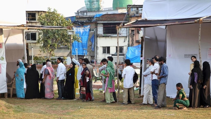Indians stand in a queue to cast their votes at a polling station in Mumbai, India, Wednesday, Oct. 15, 2014. The Indian states Haryana and Maharashtra are going to the polls Wednesday to elect representatives to their respective state Assemblies. (AP Photo/Rajanish Kakade)