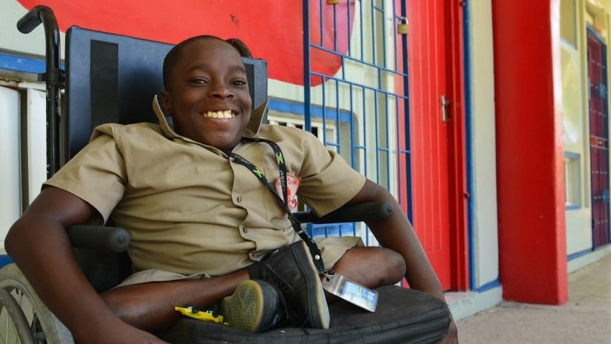 In this Oct. 7, 2014 photo, seventh-grader Andre Coleman poses in his wheelchair at his new school in the Mona neighborhood of Kingston, Jamaica. The hard-working 12-year-old with a big personality has a disabling spinal condition that does nothing to stop him from enthusiastically joining in football games with able-bodied peers. Even as they grapple with overcoming numerous challenges, hopes for the future are rising among many disabled youngsters.in Jamaica. Last week, lawmakers passed a watershed law that will, among other things, prohibit workplace discrimination and create a special tribunal to rule on complaints made by disabled citizens. (AP Photo/David McFadden)