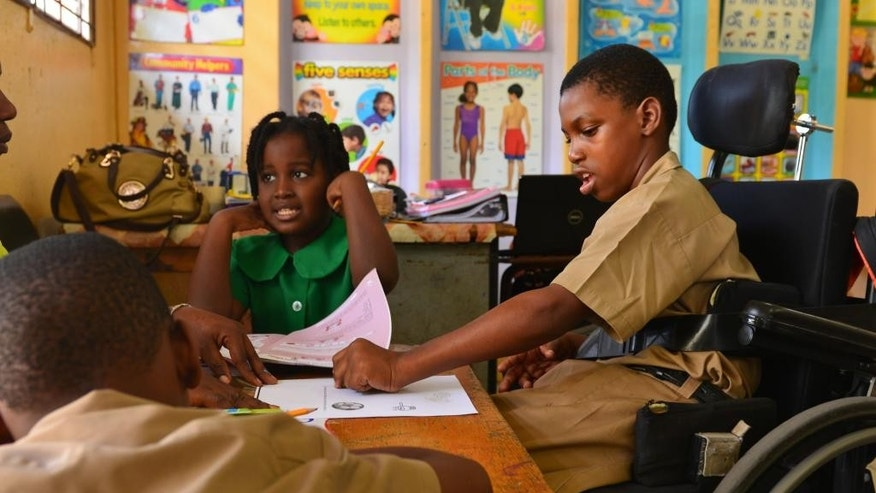 In this Oct. 7, 2014 photo, Jellani Thompson, right, colors a worksheet at the Hope Valley Experimental School in Kingston, Jamaica. Diagnosed with cerebral palsy and spina bifida, he is one of several disabled youngsters enrolled at the school founded in 1972 that integrates physically challenged students alongside able-bodied peers. Resources and basic protections for the disabled are often scarce. But that appears be slowly changing in parts of  the Caribbean after years of struggle. Jamaica last week passed a watershed law that will, among other things, prohibit workplace discrimination and create a special tribunal to rule on complaints made by disabled citizens. (AP Photo/David McFadden)