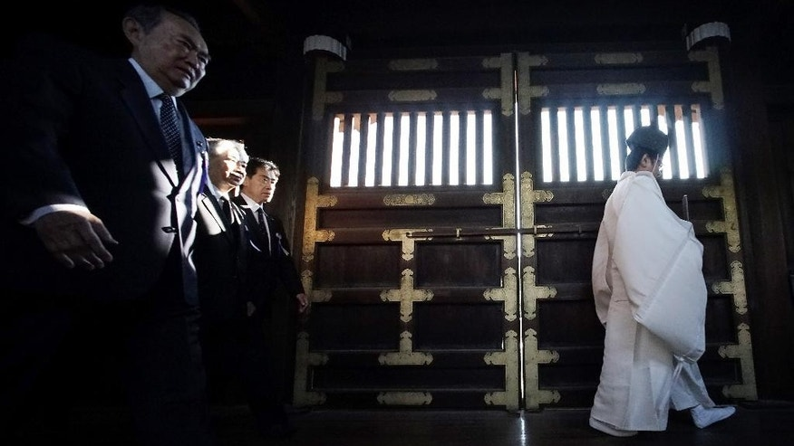 A group of Japanese lawmakers follow a Shinto priest to pay respect for the war dead at Yasukuni Shrine during an annual autumn festival in Tokyo, Friday, Oct. 17, 2014. The shrine honors war criminals, including wartime leader Hideki Tojo, among the 2.5 million war dead.  (AP Photo/Eugene Hoshiko)