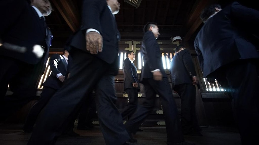 A group of Japanese lawmakers walk to pay respect for the war dead at Yasukuni Shrine during an annual autumn festival in Tokyo, Friday, Oct. 17, 2014. The shrine enshrines war criminals, including wartime leader Hideki Tojo, among the 2.5 million war dead.(AP Photo/Eugene Hoshiko)