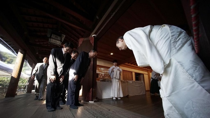 A group of Japanese lawmakers bow to a Shinto priest after paying respect for the war dead at Yasukuni Shrine during an annual autumn festival in Tokyo, Friday, Oct. 17, 2014. The shrine enshrines war criminals, including wartime leader Hideki Tojo, among the 2.5 million war dead.(AP Photo/Eugene Hoshiko)
