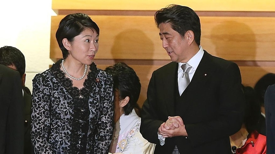 FILE - In this Sept. 3, 2014 file photo, Japan's Prime Minister Shinzo Abe, right, and his newly appointed Trade Minister Yuko Obuchi chat prior to a group photo session following the first Cabinet meeting at the prime minister's official residence in Tokyo. Obuchi was peppered with questions in parliament Thursday, Oct. 16 over her political spending in the latest scandal involving female members in Abe's Cabinet. Three other female ministers have been questioned over campaign giveaways, gaffes or alleged links to racist groups. (AP Photo/Eugene Hoshiko, File)