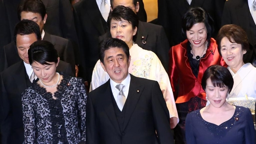 FILE - In this Sept. 3, 2014 file photo, Japan's Prime Minister Shinzo Abe, front row center, and his new Cabinet members, Trade Minister Yuko Obuchi, bottom left, Internal Affairs Minister Sanae Takaichi, bottom right, Minister in charge of Promoting Women Haruko Arimura, center behind Abe, Justice Minister Midori Matsushima, top second right, and Minister in charge of Japanese Abducted by North Korea Eriko Yamatani, top right, walk for a group photo session following the first Cabinet meeting at Abe's official residence in Tokyo. Obuchi was peppered with questions in parliament Thursday, Oct. 16 over her political spending in the latest scandal involving female members in Abe's Cabinet. Three other female ministers have been questioned over campaign giveaways, gaffes or alleged links to racist groups. (AP Photo/Eugene Hoshiko, File)