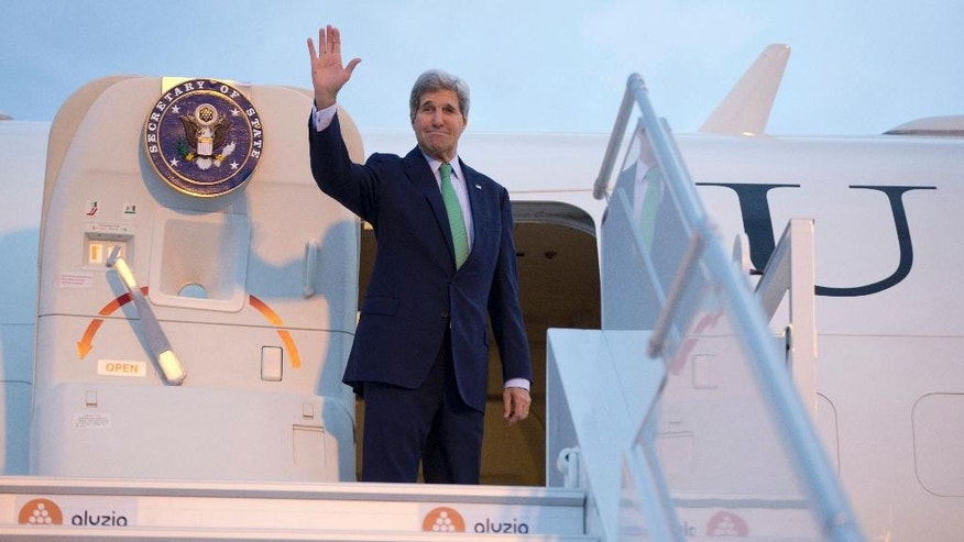 FILE - In this Oct. 15, 2014 file-pool photo Secretary of State John Kerry waves as he boards his plane at Orly Airport, south of Paris, France, en route to Vienna, Austria. The US may be the mightiest military and economic power in the world but when it comes to shuttling its top diplomat around the globe, it's beginning to look like a poor orphan. For the fourth time this year _ and the second time in three months, Kerry was forced to fly home commercially when his aging Air Force Boeing 757, known in military parlance as a C-32, was grounded on Thursday with a mechanical problem in Vienna. (AP Photo/Carolyn Kaster, File-Pool)