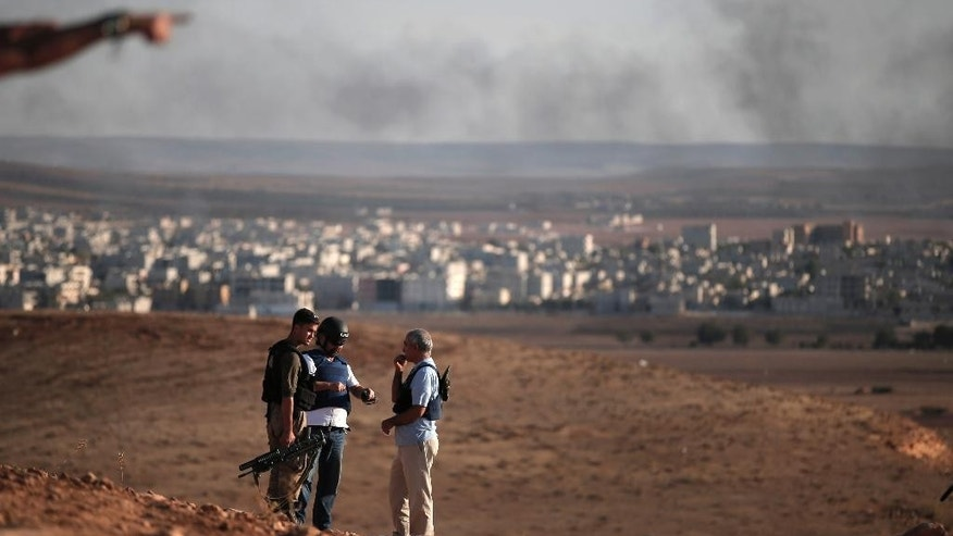 Members of the media talk with a Turkish soldier, left, on a hilltop on the outskirts of Suaruc, at the Turkey-Syria border, overlooking Kobani, Syria, background, during fighting between Syrian Kurds and the militants of Islamic State group, Wedesday, Oct. 15, 2014. Kobani, also known as Ayn Arab, and its surrounding areas, has been under assault by extremists of the Islamic State group since mid-September and is being defended by Kurdish fighters. (AP Photo/Lefteris Pitarakis)