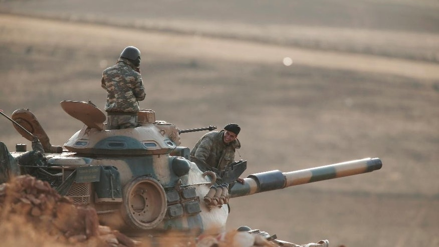 Turkish soldiers hold their positions with their tank on a hilltop on the outskirts of Suruc, at the Turkey-Syria border, overlooking Kobani, Syria, during fighting between Syrian Kurds and the militants of Islamic State group, Wednesday, Oct. 15, 2014. Kobani, also known as Ayn Arab, and its surrounding areas, has been under assault by extremists of the Islamic State group since mid-September and is being defended by Kurdish fighters. (AP Photo/Lefteris Pitarakis)