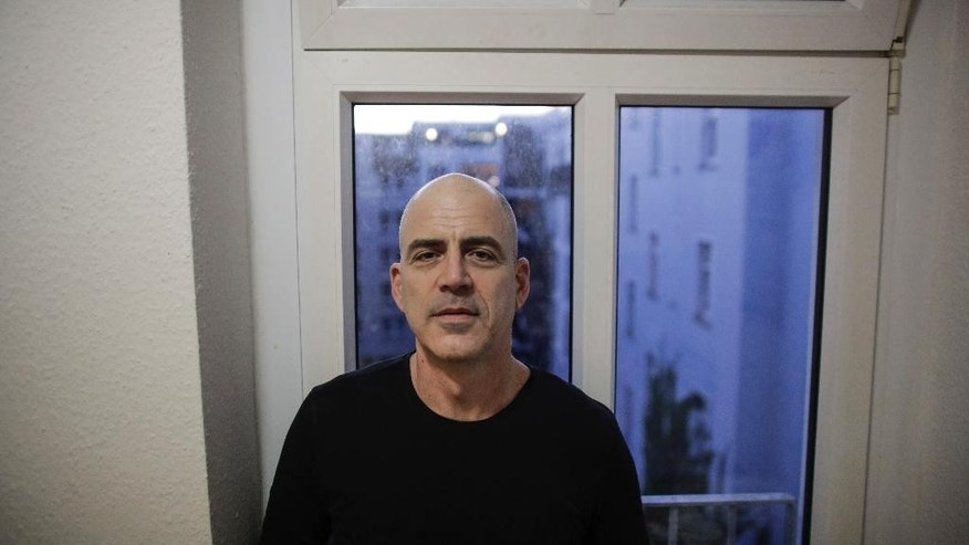 In this photo taken Tuesday, Oct. 14, 2014, Israeli Eran Levy poses for a photo prior to an interview with The Associated Press at his apartment in Berlin. The 46-year-old who moved to Berlin nine years ago, said he enjoys the calmer pace of life and the relief that his daughter is growing up far away from bomb shelters and rocket attacks. A group of young Israeli expats have unleashed a storm of controversy back home by encouraging others to join them in Berlin, touching on two of the most sensitive issues in Israel: the country's high cost of living and Jews' tortured history with Germany. (AP Photo/Markus Schreiber)