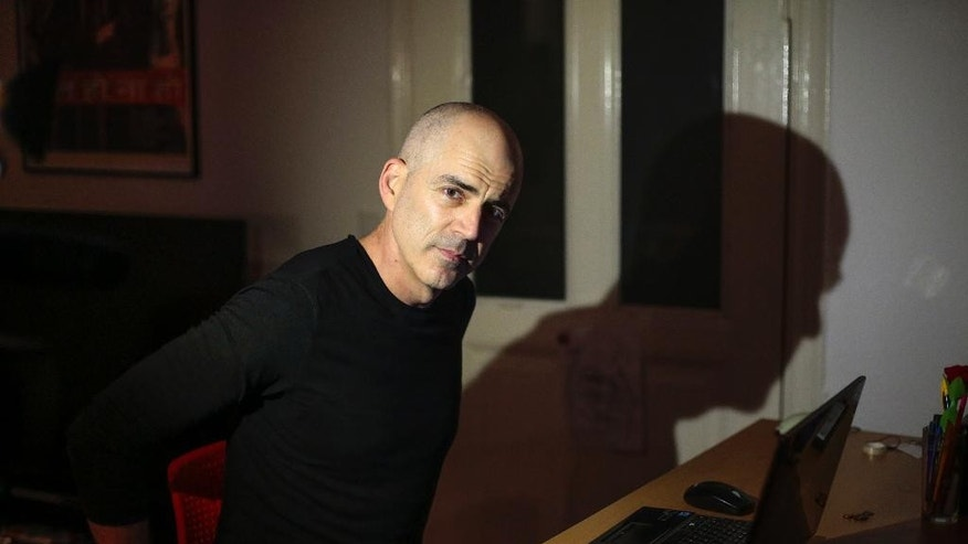 In this photo taken Tuesday, Oct. 14, 2014, Israeli Eran Levy sits in front of his computer prior to an interview with The Associated Press at his apartment in Berlin. The 46-year-old who moved to Berlin nine years ago, said he enjoys the calmer pace of life and the relief that his daughter is growing up far away from bomb shelters and rocket attacks. A group of young Israeli expats have unleashed a storm of controversy back home by encouraging others to join them in Berlin, touching on two of the most sensitive issues in Israel: the country's high cost of living and Jews' tortured history with Germany. (AP Photo/Markus Schreiber)