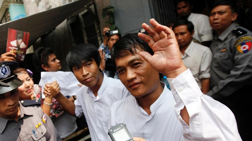 Myanmar journalists of a local weekly journal, Aung Thant, center right, and Min Wathan, center left, greet colleagues as they leave a township court Thursday, Oct 16, 2014, in Yangon, Myanmar. A Myanmar court has sentenced five people including three journalists to two years in prison - the latest in a  series of ruling that have raised concerns about press freedoms. The Pabaedan township court on Thursday charged three reporters and the journal's publisher and owner for causing public alarm. (AP Photo/Khin Maung Win)