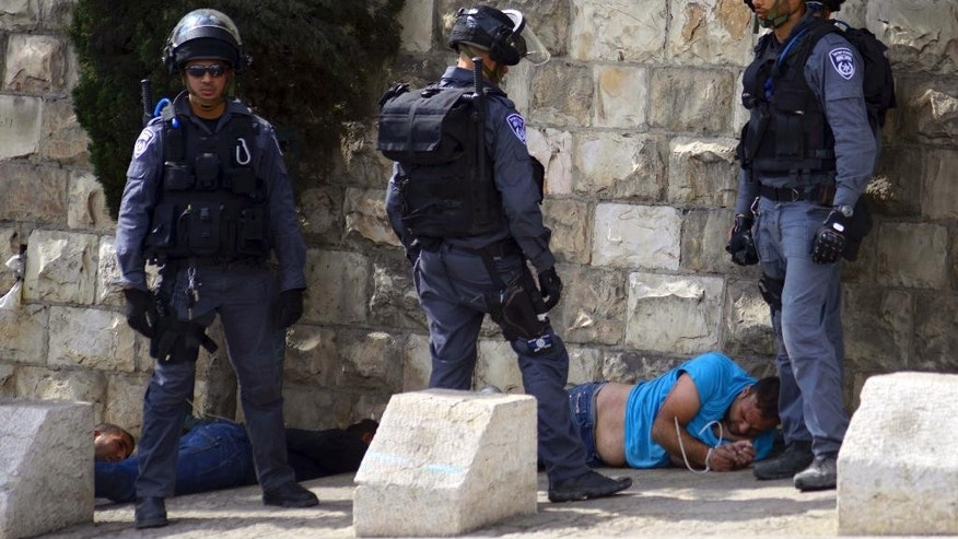 Oct. 15, 2014: Israeli police officers detain a Palestinian man during clashes near Jerusalem's old city. (AP)
