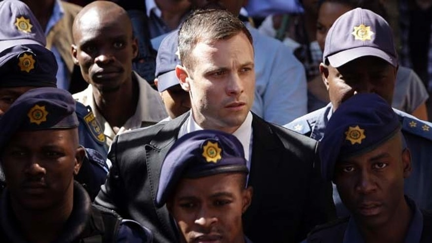 Oct. 16, 2014: Oscar Pistorius, center, is escorted by police officers as he leaves the high court in Pretoria, South Africa.