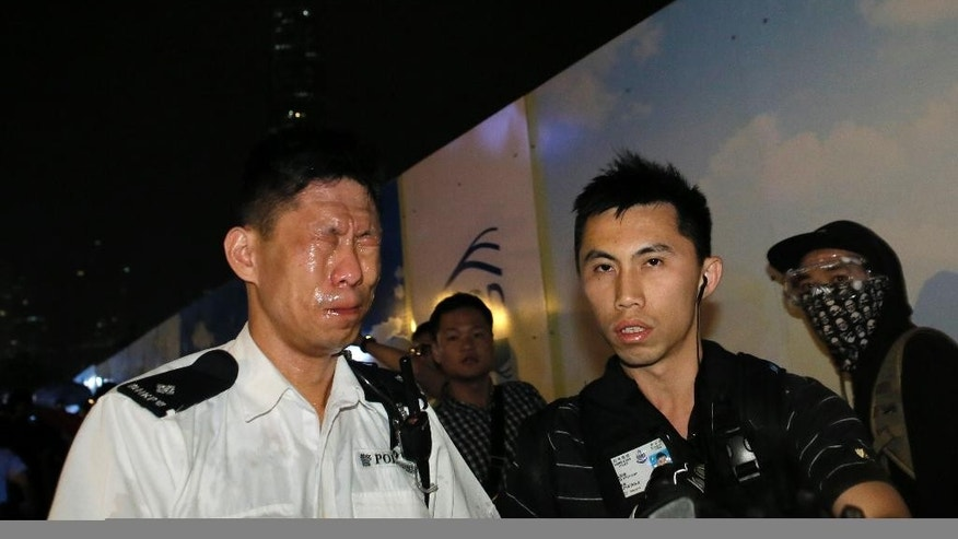 A police officer reacts after he was hit by pepper spray after a clash between protesters and police near an occupied area by pro-democracy protesters in Hong Kong early Thursday, Oct. 16, 2014. Riot police moving against activists sparked outrage after officers were seen kicking a handcuffed protester and dragging dozens of others away Wednesday in the worst violence against the pro-democracy demonstrations in Hong Kong since they began more than two weeks ago. (AP Photo/Vincent Yu)