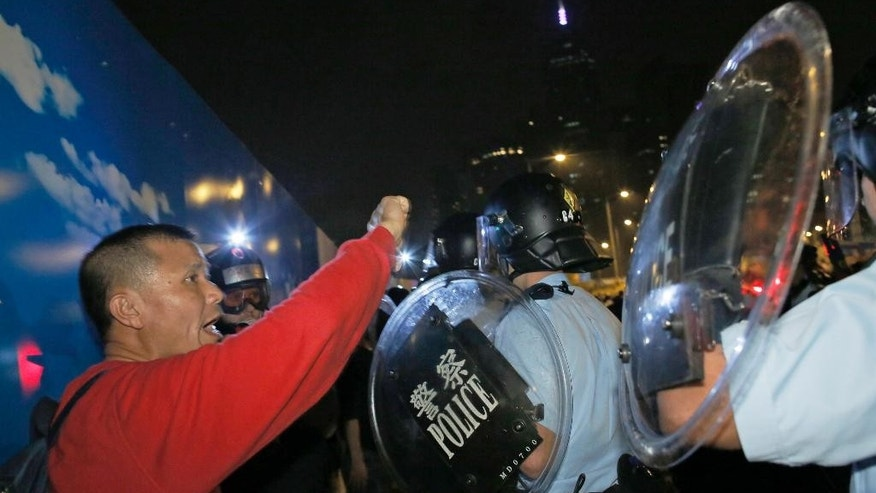 A protester shouts to riot police after a clash between protesters and police near an occupied area in Hong Kong early Thursday, Oct. 16, 2014. Riot police moving against activists sparked outrage after officers were seen kicking a handcuffed protester and dragging dozens of others away Wednesday in the worst violence against the pro-democracy demonstrations in Hong Kong since they began more than two weeks ago. (AP Photo/Vincent Yu)