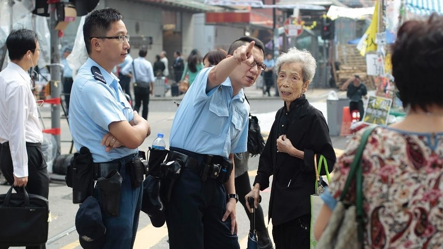 Police officers direct an elderly woman through the pro-democracy student occupied area of the Mong Kok district in Hong Kong, Thursday, Oct. 16, 2014. Police briefly scuffled with protesters camped out in Hong Kong's streets early Thursday, but held back from dismantling barricades erected by the activists pushing for greater democracy in the Chinese territory. (AP Photo/Wally Santana)