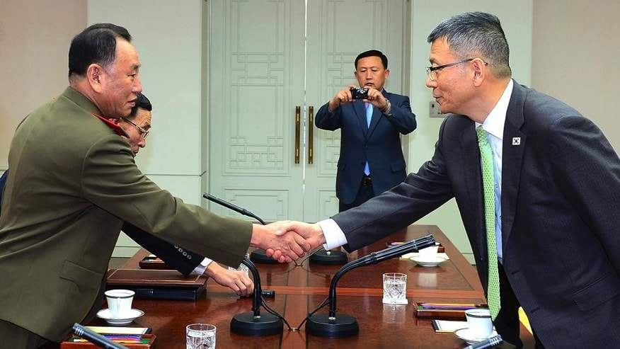 In this photo released by South Korean Defense Ministry, North Korean delegation chief Kim Yong Chol, left, shakes hands with his South Korean counterpart, Deputy Minister for National Defense Policy Ryu Je-seung during a meeting at the border village of Panmunjom, South Korea, Wednesday, Oct. 15, 2104.  The first military talks between North and South Korea in more than three years ended with no agreement Wednesday, with the rivals failing to narrow their differences on how to ease animosities following two shooting incidents last week, South Korean officials said. (AP Photo/Defense Ministry)