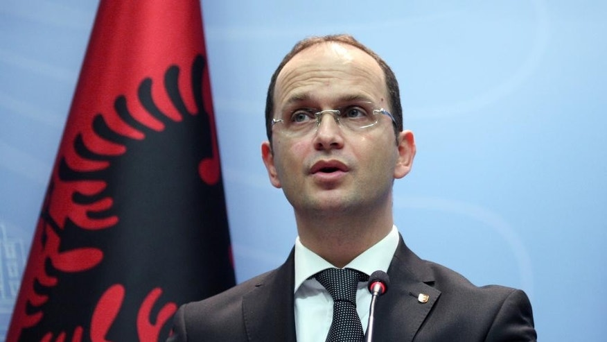 Albanian Foreign Minister Ditmir Bushati speaks at a news conference in capital Tirana, Albania Wednesday, Oct. 15, 2014, strongly denouncing anti-Albanian slogans  and the violence before, during and after the match with Serbia.  It was all about the drone Wednesday — the one that took off from an Orthodox Church in Belgrade and flew over a soccer stadium with a nationalist Albanian banner. It ignited more than a brawl between players and fans — it inflamed years of simmering tensions between Balkan rivals Serbia and Albania. (AP Photo/Hektor Pustina)