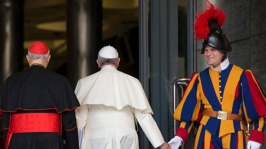 Pope Francis greets a Vatican Swiss Guard as he arrives for a morning session of a two-week synod on family issues, at the Vatican, Thursday, Oct. 16, 2014. (AP Photo/Alessandra Tarantino)