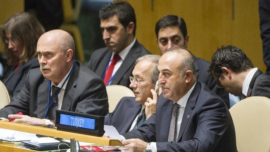 In this photo provided by the United Nations, Mevlut Cavusoglu, right, Foreign Minister of Turkey, attends a meeting of the U.N. General Assembly, Thursday, Oct. 16, 2014 at U.N. headquarters. (AP Photo/United Nations, Mark Garten)