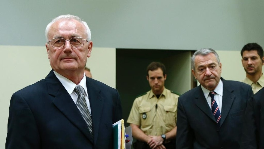 Defendants Josip Perkovic , left, and Zdravko Mustac, second right, former members of the Yugoslav secret service,  arrive for their trial in a Munich courtroom  Friday Oct. 17,  2014.  A former head of Yugoslavia's secret  service and a one-time subordinate have gone on trial in Germany over the 1983  killing of a Yugoslav dissident in Bavaria.  Zdravko Mustac and former subordinate Josip Perkovic, who later created independent Croatia's spy agency,  are both charged with being accessories to the murder of Stjepan Djurekovic. The dissident was shot and beaten on July 28, 1983 in a garage in Wolfratshausen, near Munich.     (AP Photo//Michaela Rehle,Pool)