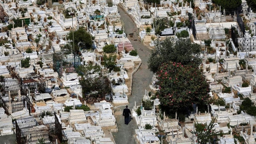 In this Oct. 14, 2014, photo, a Lebanese man, center, walks between graves at the overcrowded Bashoura cemetery for Muslim Sunnis in Beirut, Lebanon. The congested city of more than one million is cramped with cemeteries wedged into residential areas, increasingly forcing families to bury several members of the same family in one grave. Available land plots are extremely scarce and what is left is being used by developers to build luxury officers towers and apartments. (AP Photo/Hussein Malla)