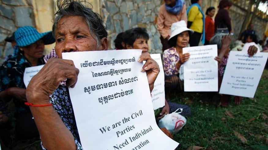 Victims in Khmer Rouge regime hold a protest to demand an individual reparation, in front of an entrance of the U.N.-backed war crimes tribunal as a hearing is held in Phnom Penh, Cambodia, Friday, Oct. 17, 2014. A U.N.-backed Cambodian tribunal began hearing the first genocide case against the country's brutal 1970s Khmer Rouge regime on Friday, another step toward justice for an estimated 1.7 million people who died from starvation, disease and execution. (AP Photo/Heng Sinith)