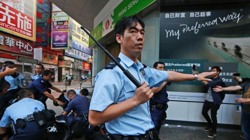 Protesters scuffle with riot policc in the occupied area in the Mong Kok district of Hong Kong Friday, Oct. 17, 2014. New scuffles broke out Friday night between Hong Kong riot police and pro-democracy activists in a district where police cleared protesters earlier in the day. The chaotic scenes unfolded hours after police moved in to clear tents, canopies and barricades at Mong Kok, a smaller protest zone across Victoria Harbor from the main occupied area in the heart of the financial district. (AP Photo/Kin Cheung)