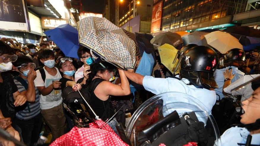 Protesters scuffle with riot police in the occupied area in the Mong Kok district of Hong Kong, late Friday, Oct. 17, 2014. New scuffles broke out Friday night between Hong Kong riot police and pro-democracy activists in a district where police cleared protesters earlier in the day. The chaotic scenes unfolded hours after police moved in to clear tents, canopies and barricades at Mong Kok, a smaller protest zone across Victoria Harbor from the main occupied area in the heart of the financial district. (AP Photo/Kin Cheung)