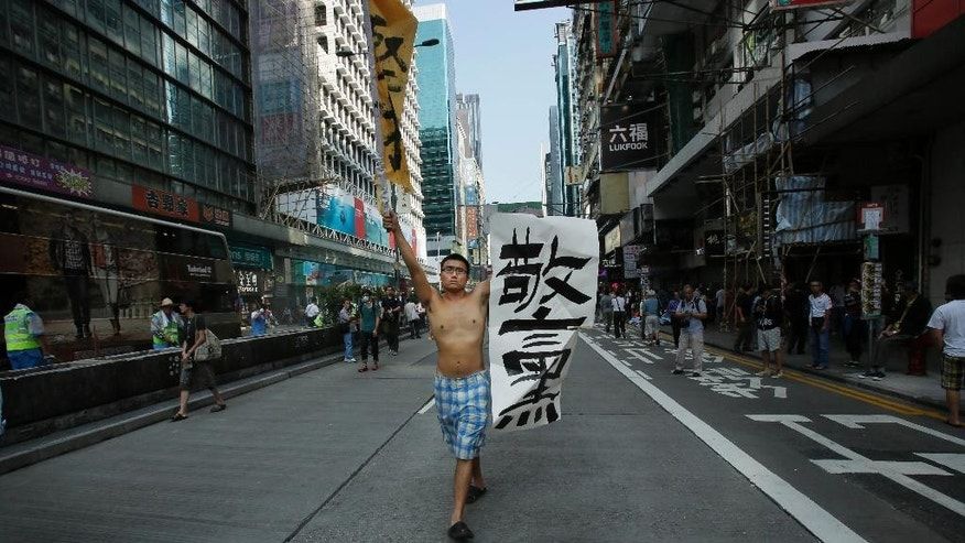 "A pro-democracy protester carries a banner that reads: ""bad police"" down an occupied section of the Mong Kok district in Hong Kong, Friday, Oct. 17, 2014. Student-led pro-democracy protests have roiled Hong Kong for 20 days - and there remains no clear endgame to the political crisis, the most tumultuous in this semiautonomous Chinese city since it returned to Chinese rule. (AP Photo/Wally Santana)"