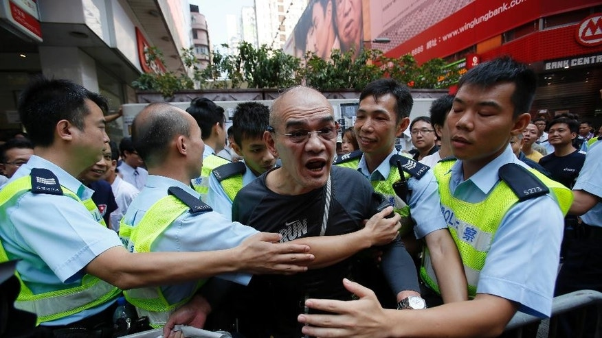 A angry man is held by police as he lashes out at pro-democracy protesters occupying a main road in the Mong Kok district of Hong Kong, Friday, Oct. 17, 2014. Student-led pro-democracy protests have roiled Hong Kong for 20 days - and there remains no clear endgame to the political crisis, the most tumultuous in this semiautonomous Chinese city since it returned to Chinese rule. (AP Photo/Wally Santana)