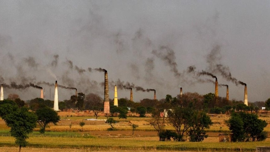 FILE- In this Tuesday, Sept. 23, 2014 file photo, smoke rises from chimneys of brick kilns on the outskirts of New Delhi, India. India launched the Air Quality Index Friday, Oct. 17, to measure air quality across the nation that is home to some of the most polluted cities in the world. It will measure eight major pollutants that impact respiratory health in cities with populations exceeding 1 million in the next five years and then gradually the rest of the country, Environment Minister Prakash told reporters. The World Health Organization said earlier this year that the Indian capital had the worst air quality in the world, surpassing Beijing, a statement that New Delhi has vehemently disputed. (AP Photo/Altaf Qadri, File)
