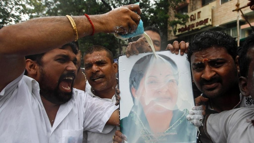 A supporter pours milk over a portrait of former chief minister of Tamil Nadu state Jayaram Jayalalitha, a former movie star, as he celebrates with others the news of bail being granted to her, outside their party office in Chennai, India, Friday, Oct. 17, 2014. India's top court Friday granted temporary bail to the charismatic southern Indian politician who was sentenced to four years in prison after being found guilty of corruption last month. The 65-year-old requested bail because she said she suffered from diabetes and high blood pressure and needed medical attention. (AP Photo/Arun Sankar K)