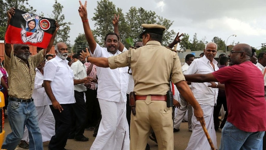 A police officer tries to disperse supporters of former chief minister of Tamil Nadu state Jayaram Jayalalitha, a former movie star, outside the prison where she is being held in Bangalore, India, Friday, Oct. 17, 2014. India's top court Friday granted temporary bail to the charismatic southern Indian politician who was sentenced to four years in prison after being found guilty of corruption last month. The 65-year-old requested bail because she said she suffered from diabetes and high blood pressure and needed medical attention. (AP Photo/Aijaz Rahi)
