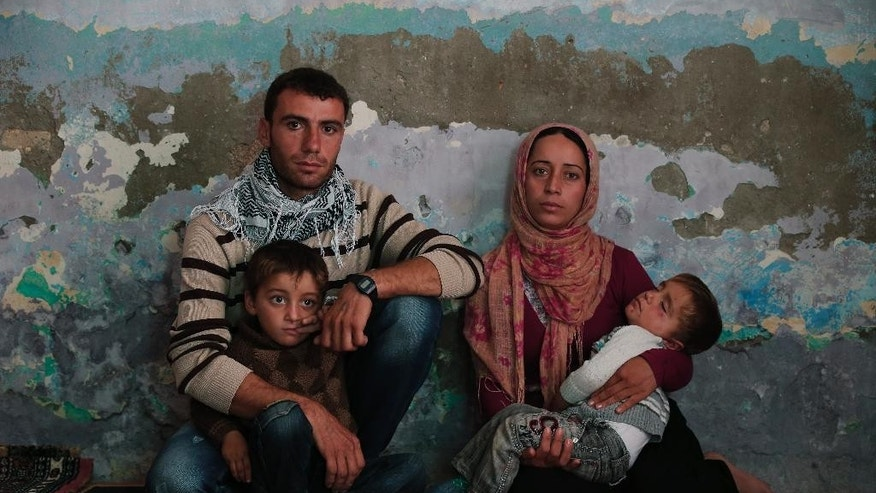 Syrian Kurdish fighter Delkhwaz Sheikh Ahmad, 22, sits with his wife Siham, 23, and their two sons, Dilyar, left, 3 and Ibrahim, 2, right, at his brother's house in Suruc, on the Turkey-Syria border, as he prepares to leave for Kobani, Syria, to rejoin the fighting, Friday, Oct. 17, 2014. Sheikh Ahmad is a member of the People's Protection Units, also known as YPG and is fighting against militants of the Islamic State group in Kobani, Syria. Every few weeks, he takes a couple of days to cross the border into Turkey to visit his family that had evacuated. Kobani, also known as Ayn Arab, and its surrounding areas, has been under assault by extremists of the Islamic State group since mid-September and is being defended by Kurdish fighters. (AP Photo/Lefteris Pitarakis)