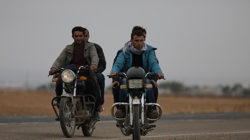 Syrian Kurdish fighter Delkhwaz Sheikh Ahmad, right, 22, rides a motorcycle on the outskirts of Suruc, on the Turkey-Syria border, as he and other fighters try to approach the border to cross into Syria to rejoin the fighting In Kobani, Friday, Oct. 17, 2014. The father of two is a member of the People's Protection Units, also known as YPG and is fighting against militants of the Islamic State group in Kobani, Syria. Every few weeks, he takes a couple of days to cross the border into Turkey to visit his family that had evacuated. Kobani, also known as Ayn Arab, and its surrounding areas, has been under assault by extremists of the Islamic State group since mid-September and is being defended by Kurdish fighters. (AP Photo/Lefteris Pitarakis)