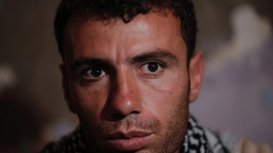 Syrian Kurdish fighter Delkhwaz Sheikh Ahmad, 22, sits at his brother's house in Suruc, on the Turkey-Syria border, Friday, Oct. 17, 2014 as he prepares to leave for Kobani, Syria, to rejoin the fighting, The father of two is a member of the People's Protection Units, also known as YPG and is fighting against militants of the Islamic State group in Kobani, Syria. Every few weeks, he takes a couple of days to cross the border into Turkey to visit his family that had evacuated. Kobani, also known as Ayn Arab, and its surrounding areas, has been under assault by extremists of the Islamic State group since mid-September and is being defended by Kurdish fighters. (AP Photo/Lefteris Pitarakis)