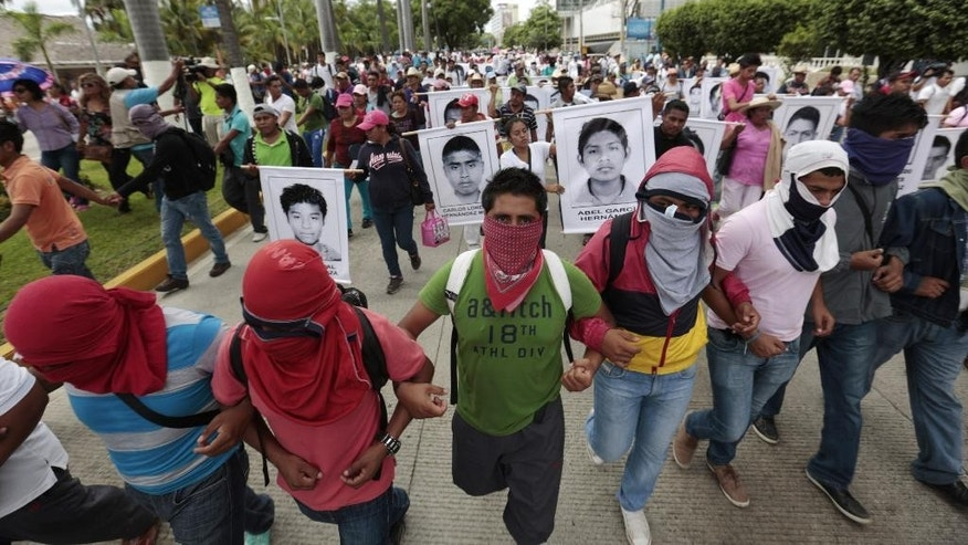 Masked demonstrators march with photographs of missing students and chant slogans to protest the disappearance of 43 students from the Isidro Burgos rural teachers college in Acapulco, Guerrero state, Mexico, Friday, Oct. 17, 2014. Investigators determined that 28 sets of human remains recovered from a mass grave discovered last weekend outside Iguala, in Guerrero state, were not those of any of the youths who haven't been seen since being confronted by police in Iguala on Sept. 26. (AP Photo/Eduardo Verdugo)