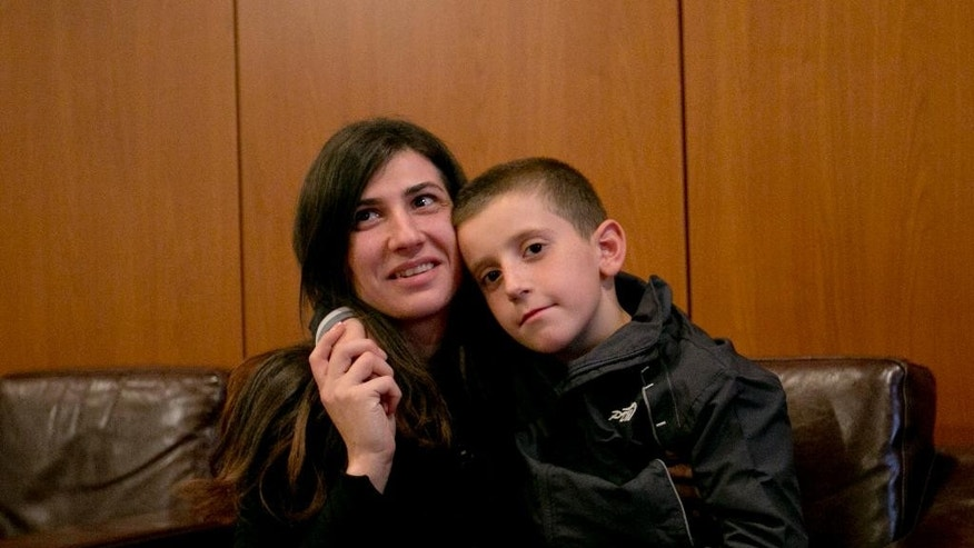 Erion Zena an 8 year old boy hugs his mother Pranvera Abazi during their reunion at Kosovo's main airport upon his return to Kosovo's capital Pristina on Wednesday, Oct. 15, 2014. Kosovo's Prime Minister says the country's intelligence and security forces have returned an 8-year-old ethnic Albanian boy to his mother in Kosovo after he was taken by his jihadi father to Syria. (AP Photo/Visar Kryeziu)