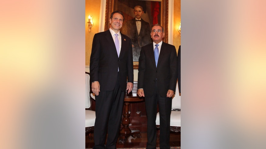 In this photo released by the Dominican Republic presidential office, New York Governor Andrew Cuomo, left, poses for a photo with President Danilo Medina at the presidential palace in Santo Domingo, Dominican Republic, Friday, Oct. 17, 2014.  Cuomo is making campaign visits to Puerto Rico and the Dominican Republic, returning to New York late today. (AP Photo/DR presidential office)