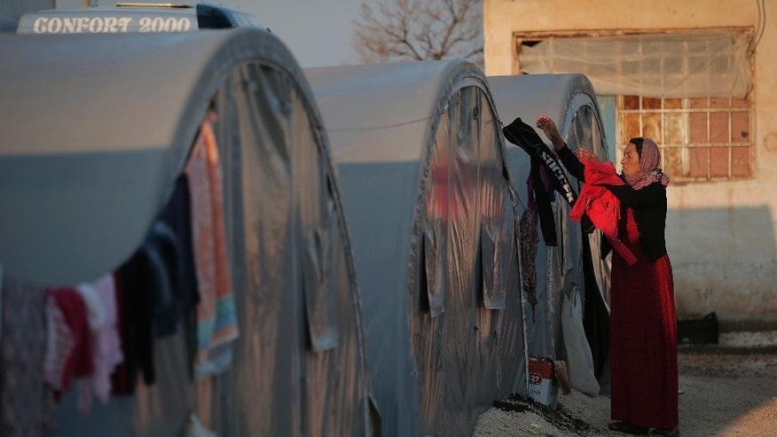 A Syrian Kurdish refugee who fled fighting in Kobani, Syria, with her family, hangs clothes to dry outside the family tent at a refugee camp in Suruc, on the Turkey-Syria border, Friday, Oct. 17, 2014. Kobani, also known as Ayn Arab, and its surrounding areas, has been under assault by extremists of the Islamic State group since mid-September and is being defended by Kurdish fighters. The onslaught has forced more than 200,000 people to flee across the border into Turkey. (AP Photo/Lefteris Pitarakis)