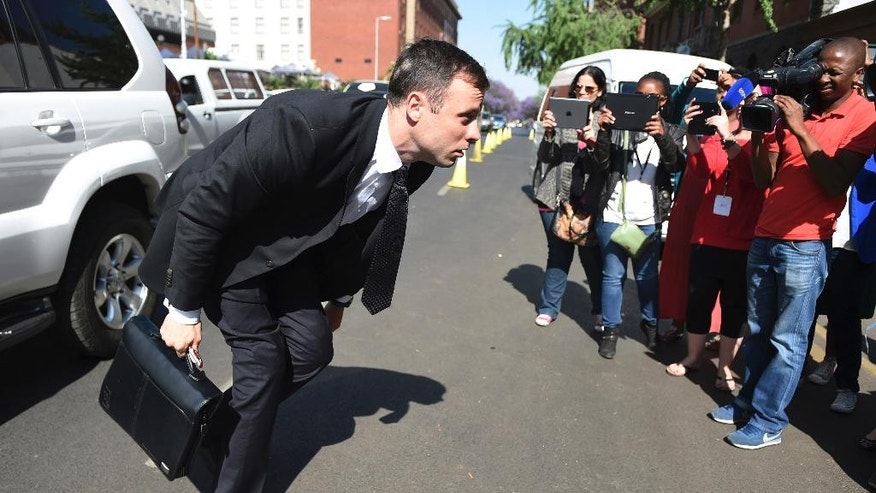 Oscar Pistorius adjusts trouser as he arrives at the high court in Pretoria, South Africa, Friday, Oct. 17, 2014. Following the testimony hearing, which is expected to end this week, Judge Thokozile Masipa will rule on what punishment Pistorius must serve after convicting him of culpable homicide for shooting his girlfriend Reeva Steenkamp through a toilet door in his home. (AP Photo)